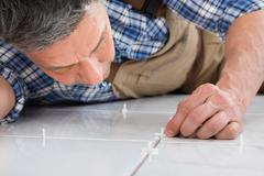 Close-up Of A Handyman Lying On Floor Placing Spacers Between Tiles - stock photo