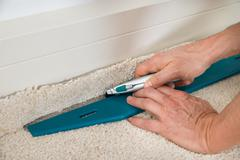 Close-up Of A Craftsman Cutting Carpet With Cutter - stock photo