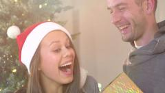 Young man surprising his girlfriend with a gift box - stock footage