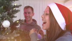 Happy couple hanging baubles on Christmas tree - stock footage