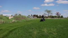 Lawn tractor driver cutting nice green lawn Stock Footage