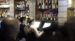 Bartenders using computer behind bar at club slow motion NYC Stock Footage