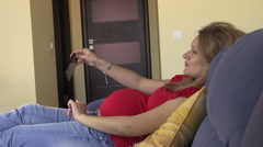 Playful pregnant woman take self portrait photos on mobile phone Stock Footage
