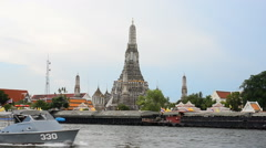 Long-tailed boat quay across the Wat Arun temple of porcelain Pagoda Stock Footage