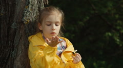 Girl tearing off petals of a daisy. Girl sitting under a tree Stock Footage
