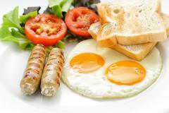 American breakfast with fried eggs, tomatoes, fried ham, beans  and sausage - stock photo
