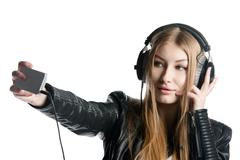 Young model in wired headphones listening music and making selfie Stock Photos