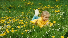 Child lying on the grass among yellow flowers. Zooming Stock Footage