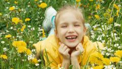 Laughing girl lying in the grass and looking at camera. Zooming Stock Footage