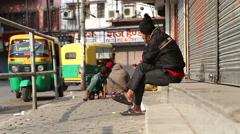 Indian man sitting at sidewalk in Jodhpur, with children playing aside. Stock Footage