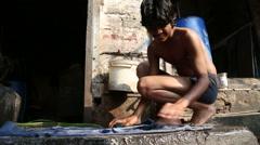 Stock Video Footage of Boy scrubbing laundry at street floor in Jodhpur, closeup.