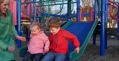 Little kids sliding and holding hands Stock Footage