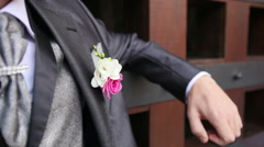 Groom in wedding suit with flower snaps fingers Stock Footage