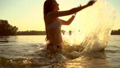 Beauty summer model girl splashing water in the river Stock Footage