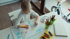 Preschooler girl laughing. Portrait child painting a picture. Looking at camera Stock Footage