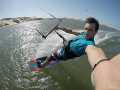 Stock Photo of SELFIE: Kiteboarder riding in flat lagoon in Brazil