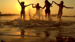 Girls running and playing in water at the beach Stock Footage