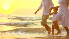 Young family with little daughter walking along coastline - stock footage