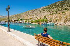 Young lady in blue sitting on bench, Greece Stock Photos
