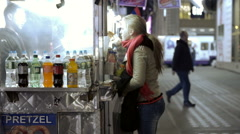 woman purchasing pretzel from food cart at night in slow motion Times Square NYC - stock footage