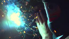 Worker welding metal by electrode with bright electric arc - stock footage