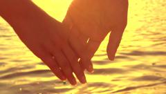Couple holding hands over blinking sea background - stock footage