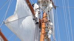 Sailors in modern uniform unleash the sails. Stock Footage