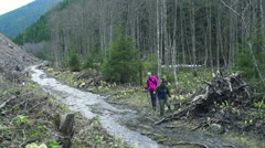 Two female hikers walking along the mountain stream slow motion Stock Footage