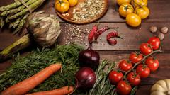 An abundance of vegetables and spices closeup on wooden table tomatoes, pumpkins Stock Photos
