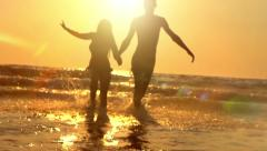 Happy young couple running out of the sea over sunset Stock Footage