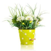 Bouquet from artificial flowers arrangement centerpiece in yellow metal bucke - stock photo