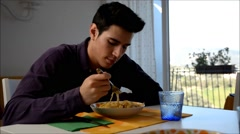 Handsome distracted young man sitting enjoying his meal of spaghetti - stock footage