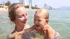 young blonde mother bathes little daughter in sea - stock footage