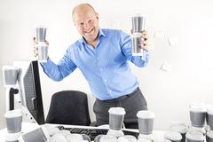 Happy businessman drinks too much coffee - stock photo