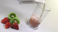 Woman making kiwi strawberry smoothie drink using stick hand blender Stock Footage