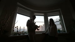 Young parents playing with the baby at the window, the silhouette Stock Footage