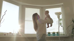 Young woman,holding her baby hands and kissing,sun lens flare Stock Footage