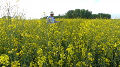 Senior farmer in rapeseed field Stock Footage