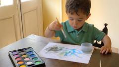 Portrait of little boy painting with watercolors Stock Footage