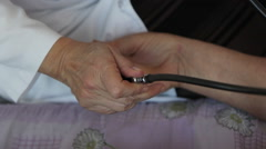 Pulse measurement: doctor measures the pressure of the old lady - patient Stock Footage