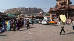 People and vehicles passing down the street beneath Mehrangarh fort. Stock Footage
