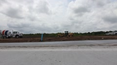 Concrete Truck Drives Over Undeveloped Land Toward Construction Site Stock Footage