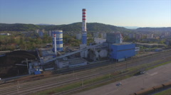 AERIAL: Freight train transporting the cargo pass the heating plant Stock Footage