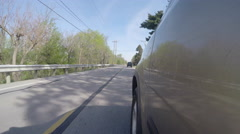 Vehicle traveling past road construction crew side mounted camera Stock Footage