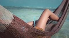 Girl on hammock drinks coconut Stock Footage