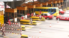 Taxi and other cars at turnpike booth gate, paying for toll road entrance Stock Footage