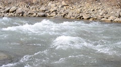 Mountain river with water quickly flowing along stony river bank Stock Footage