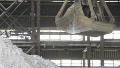 Clamshell bucket crane pour white granular on mound Stock Footage