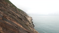 Devil's peak rocky shore, misty crag landscape against foggy horizon Stock Footage