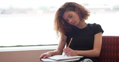 Female college student writing in notepad with pencil 4k Stock Footage